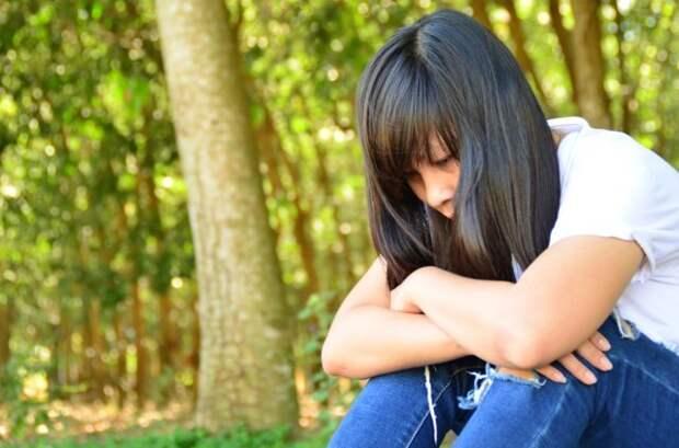 грустная девушка сидит одна