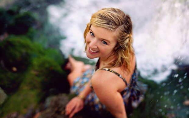 Обои Веселая девушка в платье сидит возле водопада на рабочий стол