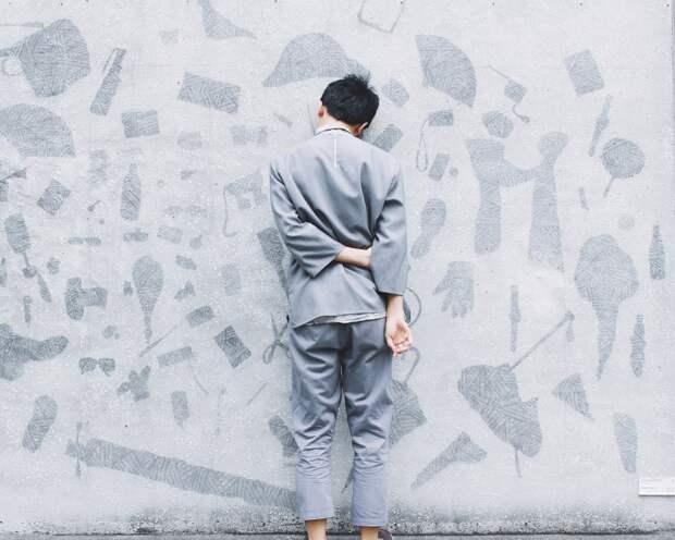 Человек стоит лицом к стене