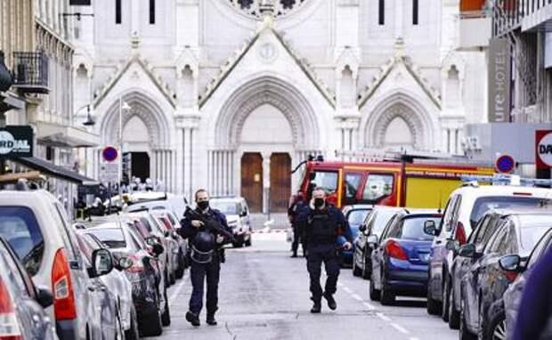 На фото: полицейские возле храма в Ницце, где вооруженный ножом неизвестный напал на людей