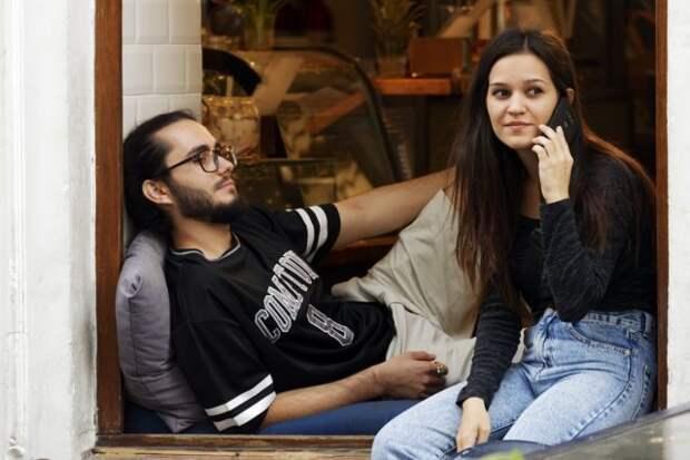 девушка сидит с телефоном рядом с парнем