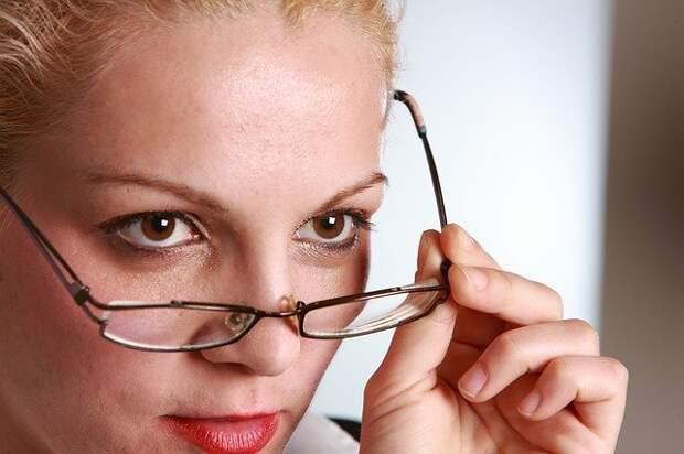 женщина снимает с лица очки