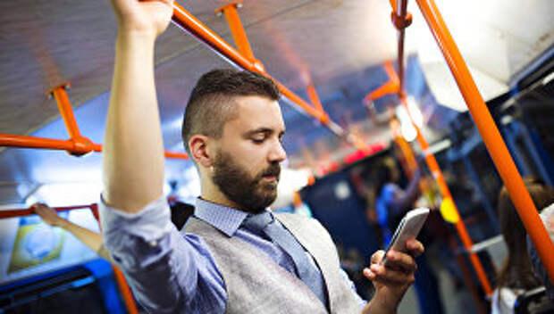 Пассажир в автобусе пользуется смартфоном
