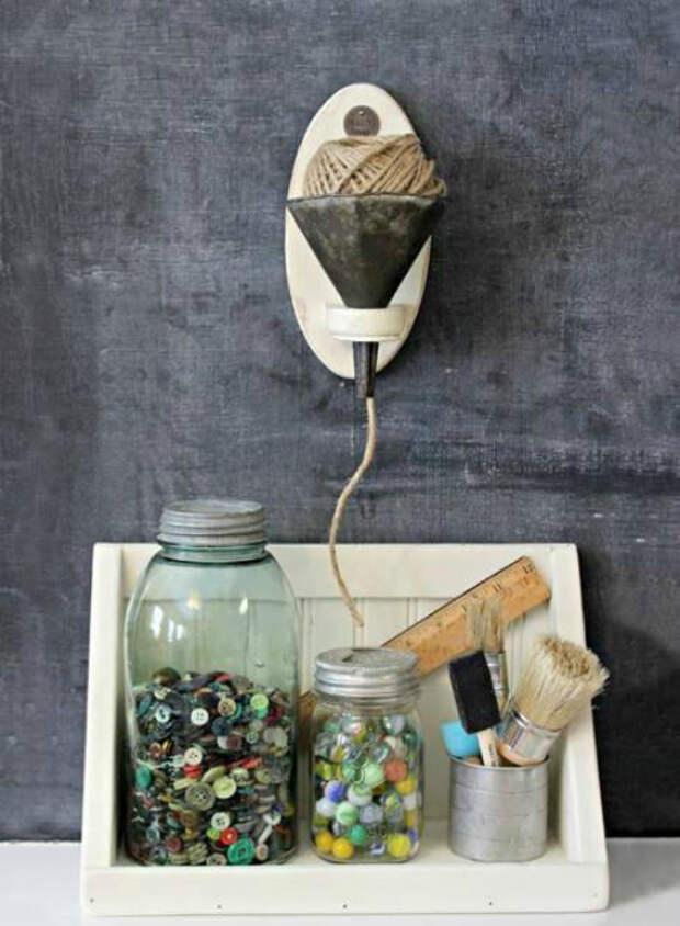 С помощью старой кухонной лейки, металлической чашки и стеклянных банок можно оборудовать уголок для творчества.