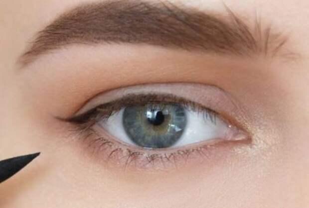 девушка рисует стрелку на глазах