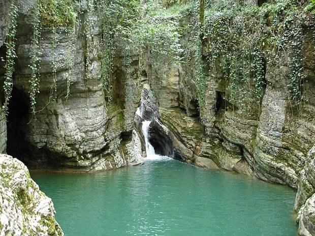 15. Агурские водопады Водопады находятся в Хостинском районе Сочи, образовались они естественным путем благодаря течению реки Агура, которая начинается на склонах хребта и бурным потоком бежит к Черному морю. Самый красивый водопад — Нижний Агурский, который включает в себя два каскада. Верхний падает с высоты 18 метров, нижний — 12 метров. И вот этот столп воды, которая летит с 30-метровой высоты, рушится вниз и превращается в чистейший бассейн с прозрачной голубой водой. Вокруг водопадов расположены ущелья, которые покрыты густой растительностью.