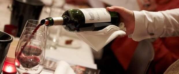 официант наливает в бокал красное вино