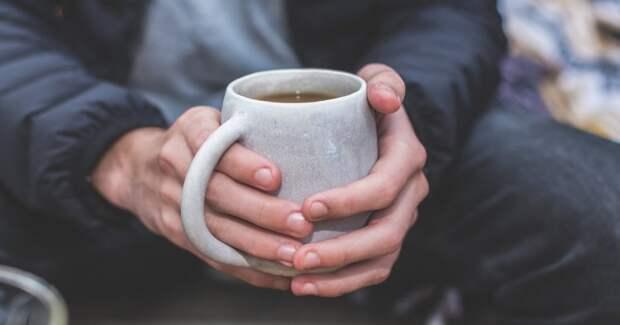 Мужчина держит кружку с горячим чаем