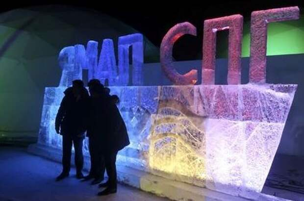 """People pose in front of an ice sculpture installation at Yamal LNG, Russia's second liquefied natural gas plant, which is under construction in the Arctic port of Sabetta, Yamalo-Nenets district, Russia December 8, 2017. The installation reads, """"Yamal LNG"""". REUTERS/Oksana Kobzeva"""