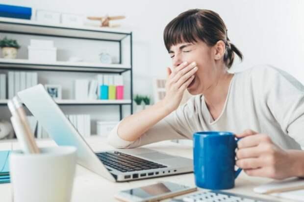 девушка с чашкой зевает перед ноутбуком