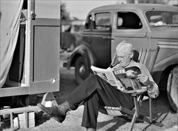 Турист читает журнал возле своего дома-трейлера в трейлерном парке, Сарасота, Флорида, январь 1941 года