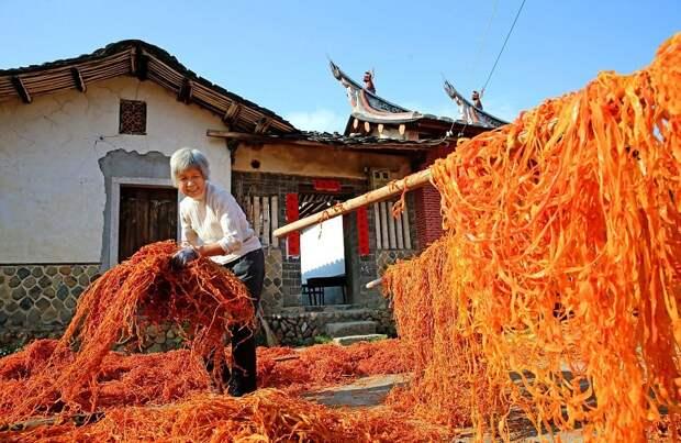 Восхитительный вид: крыши китайской деревни покрываются оранжевым цветом