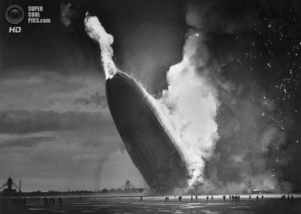 США. Лейкхёрст, Нью-Джерси. 6 мая 1937 года. Пылающий немецкий дирижабль «Гинденбург». В катастрофе, случившейся при посадке после 60-часового рейса из Германии погибло 36 человек. На этом регулярные пассажирские перевозки на дирижаблях прекратились. (AP Photo)