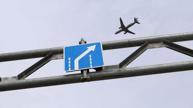 Самолет пролетает над автомобильным указателем