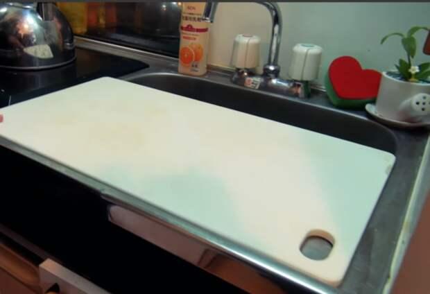 Вместо столешницы девушка использует разделочную доску, установленную на раковине. | Фото: youtube.com.
