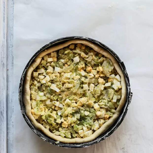 Наполняем наш пирог капустной начинкой, для этого равномерно распределяя ее по всей площади пирога.