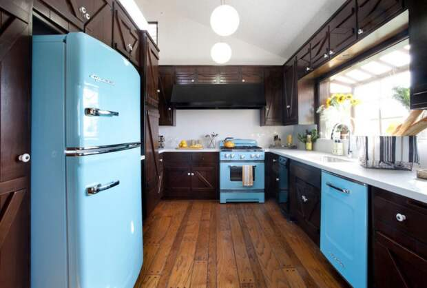 Темный интерьер кухни оживает за счет яркой и блестящей техники.