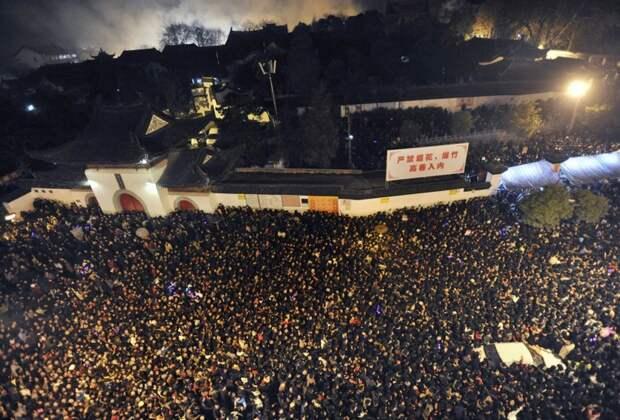 Верующие ждут у буддийского монастыря Гуйюань в Ухане, чтобы принести жертвы на пятый день Нового года по китайскому лунному календарю. Сотни миллионов человек посещают монастырские ярмарки и запускают фейерверки во время празднеств. китай, люди, население