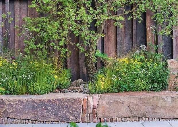 Выложите по всему периметру посадки каменные блоки и насыпьте внутрь садовую землю - получится приподнятый цветник. А если вы дополните ансамбль светильниками, в темное время суток и без того красивый уголок превратится в сказочный оазис.