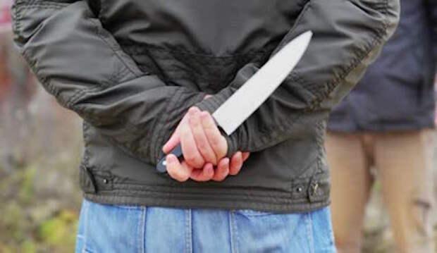 Мужчина держит нож за спиной