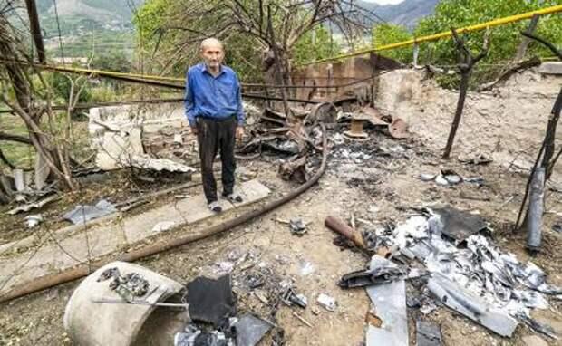 На фото: мужчина во дворе своего дома после обстрела азербайджанскими ВС.