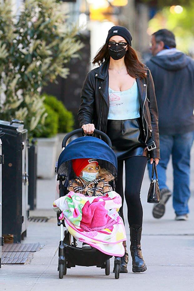 Маска, кожанка и мини: Ирина Шейк в провокационном образе на прогулке с дочкой