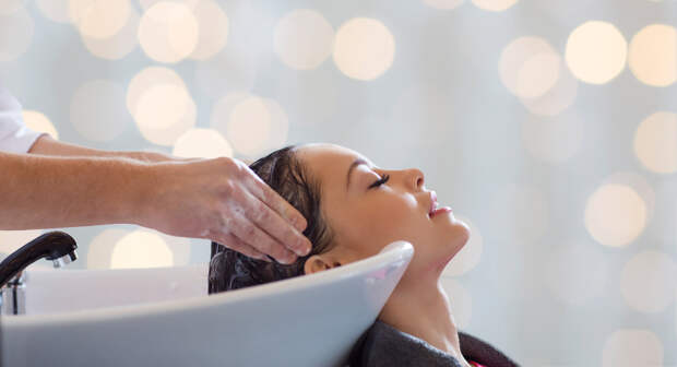 beauty salon, hair care and people concept - hairdresser hands washing happy young woman head over holidays lights background