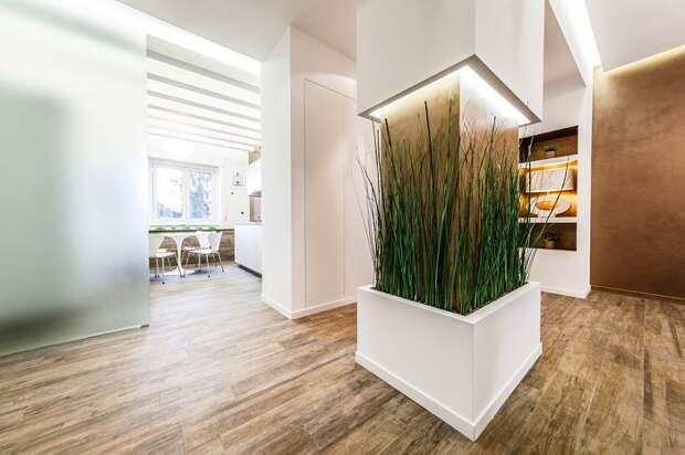 Колонна с неоновой подсветкой в интерьере современного жилища, украшенная декоративными растениями.