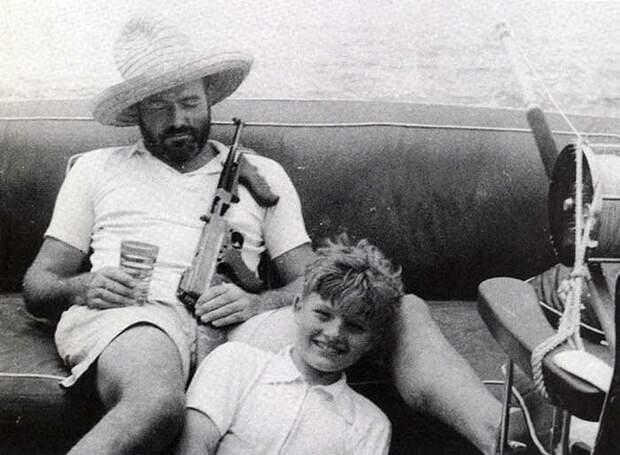 Эрнест Хемингуэй отдыхает в своей лодке с пистолетом-пулеметом Томпсона и сыном Джеком знаменитости, исторические фотографии, история, редкие фотографии, фото