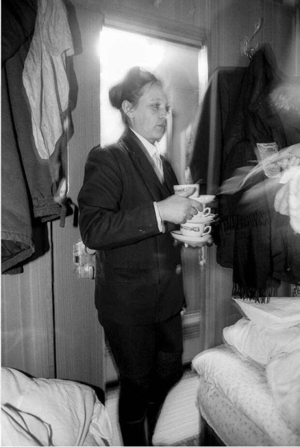 Проводница приносит чай в купе.