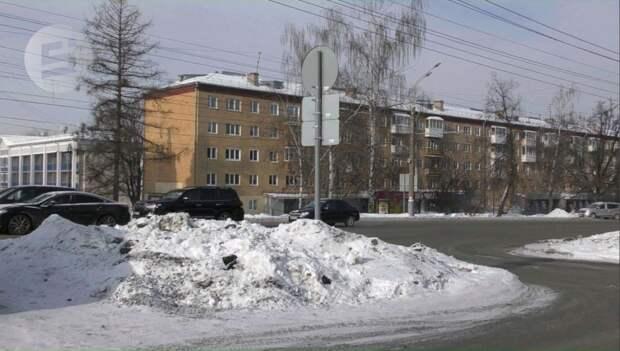 На парковке у ТЦ «Сигма» рабочие зарыли в снег мешки с неизвестными отходами