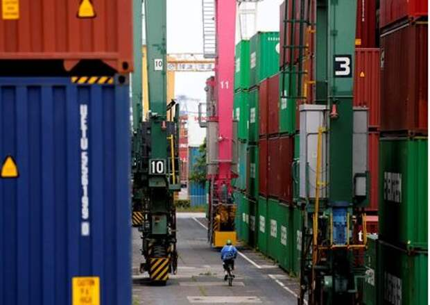 Человек на велосипеде проезжает мимо контейнеров в промышленном порту Токио, Япония, 22 мая 2019 года. REUTERS/Kim Kyung-Hoon