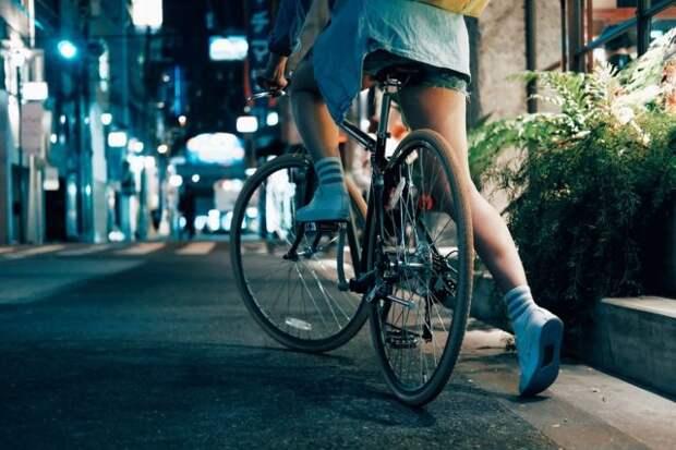 девушка едет на велосипеде по ночной улице