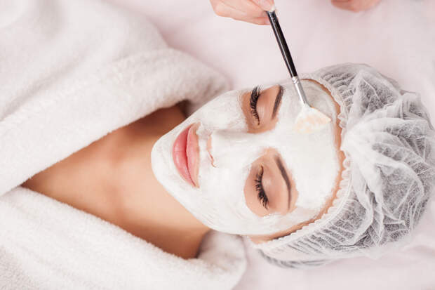 Beautiful young woman is getting facial mask at spa. She is lying and relaxing. Her eyes are closed with pleasure. The cosmetologist is applying cream on her face with brush
