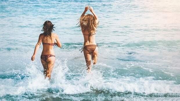 две девушки заходят в океан