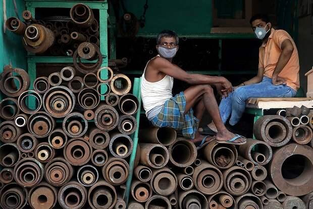 Торговцы железными трубами на рынке в Калькутте, Индия. Фото: REUTERS