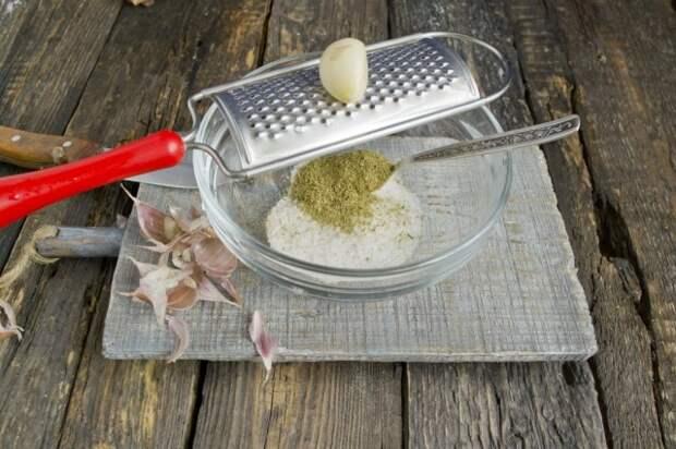 В миску насыпаем соль, специи и натираем чеснок