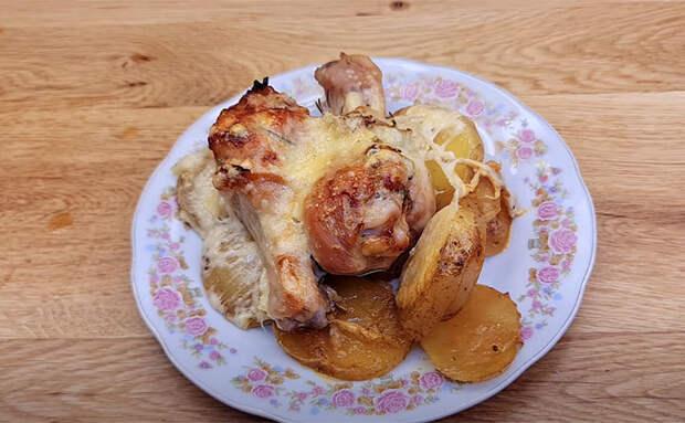 Кладем куриные голени поверх картошки и закрываем фольгой: гарнир и горячее готовы за 50 минут