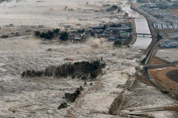 Мощные потоки воды идут вглубь суши в прибрежных районах Иваньума, префектура Мияги