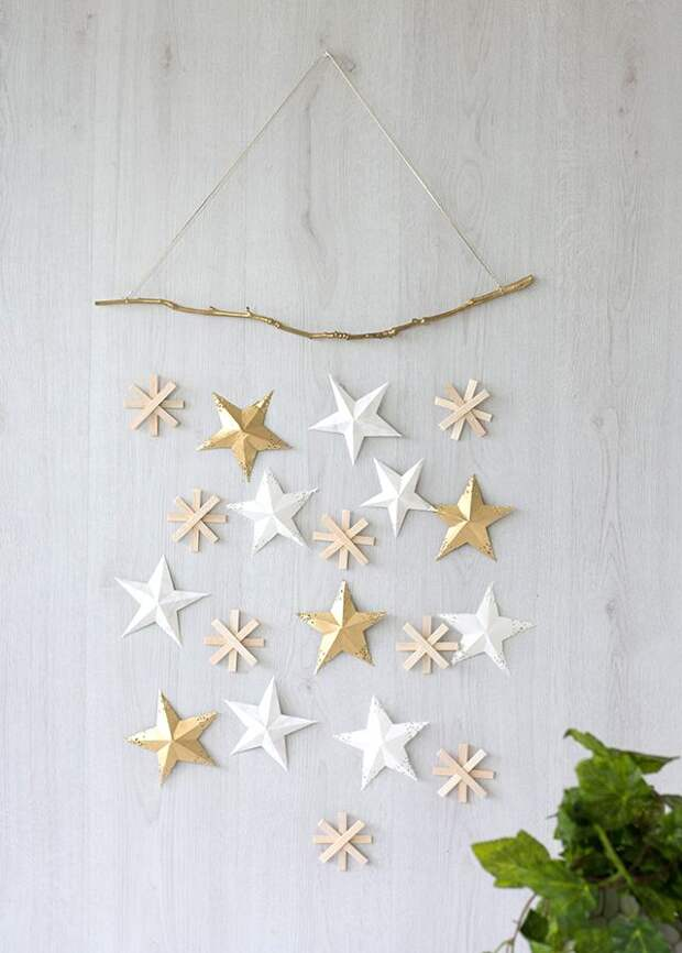 Изящное и праздничное украшение на стену из бумажных звездочек разных размеров и цветов