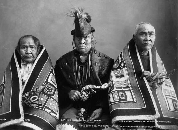 Мужчины из племени чилкат. Слева направо: Человек-обезьяна; знахарь Скан-Ду и известный индийский гид Инд-А-Янек (Сватка). Они держат в руках церемониальные погремушки и покрыты одеялами чилкат, сотканными из крашеной коры кедра и украшенными клановыми гербами. Церемониальные одежды предназначены для церемонии потлача, когда племена дарят своим гостям ценные подарки. 1907 г.