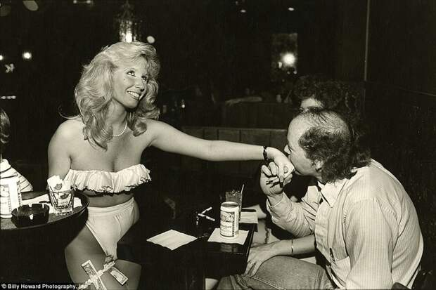 Посетитель бара целует руку официантке 80-е, сша, фотография
