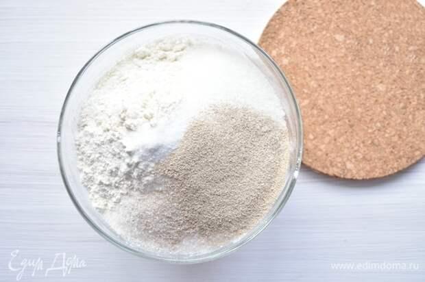 Муку дважды просеять, добавить сахар, соль, дрожжи. Перемешать.