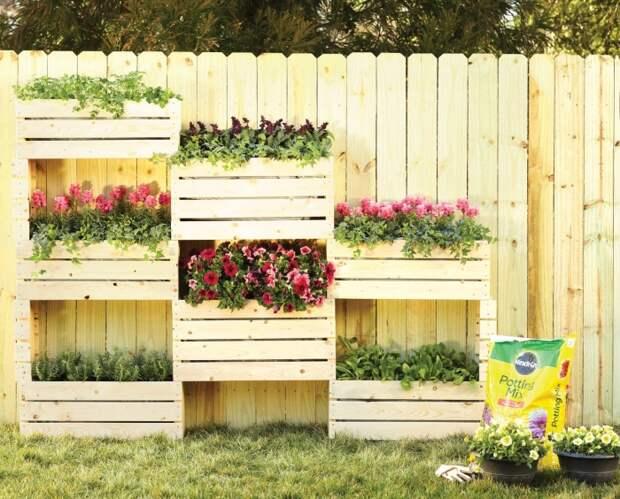 Вертикальная грядка на заборе даёт возможность выращивать растения и цветы даже на небольшом дачном участке.