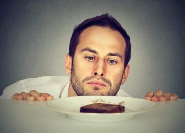 Мужчина смотрит на тарелку с едой