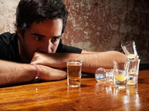 мужчина сидит за столом с рюмками