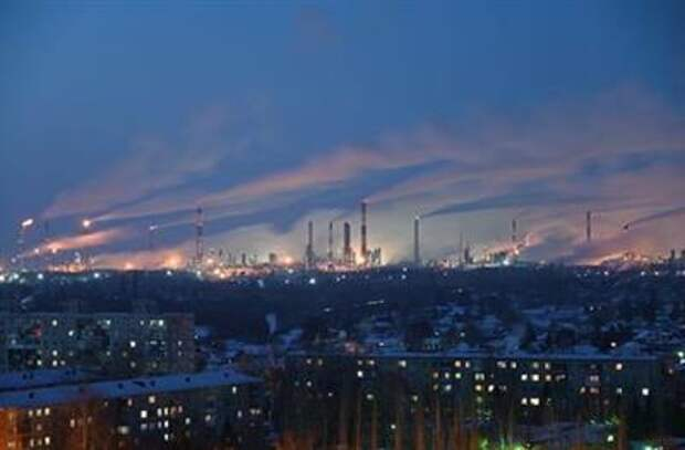 A general view shows a local oil refinery behind residential buildings in Omsk, Russia February 10, 2021. REUTERS/Alexey Malgavko