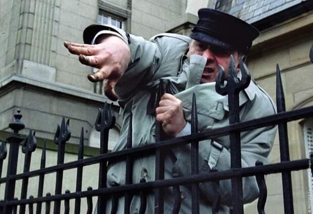 Владимир Жириновский за оградой российского консульства забрасывает землей и камнями еврейских студентов, обвинивших его в антисемитизме. Страсбург, 11 апреля 1994 год