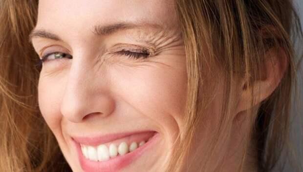 девушка подмигивает левым глазом и улыбается