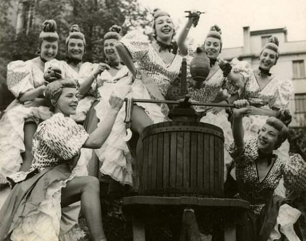 Девушки забавляются изготовлением вина.